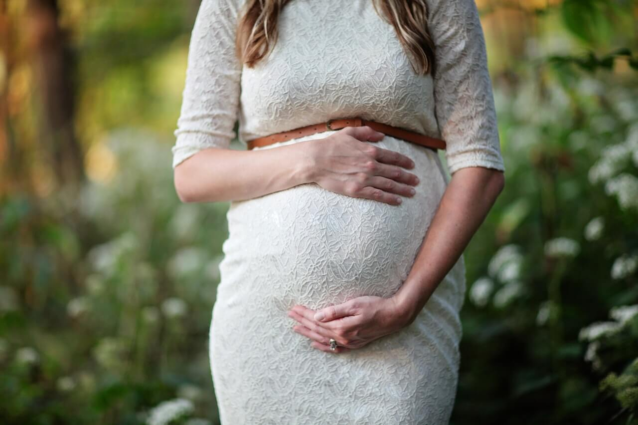 pregnant woman in white dresss holding bump